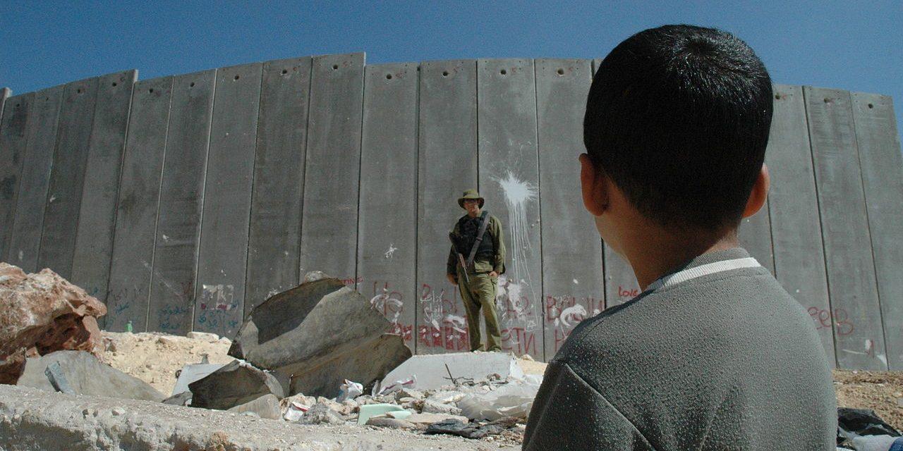 Un niño palestino mira a un soldado israelí junto al muro ilegal es West Bank, Palestina