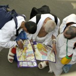 Muslim pilgrims look at a map as they ar
